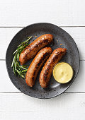 Three sausages in a plate with a side of dijon mustard sauce and seasoning