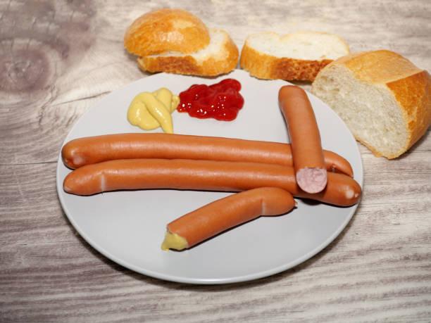 0721 Würstchen mit Senf, Ketchup und Brötchen auf einem Holztisch – Foto