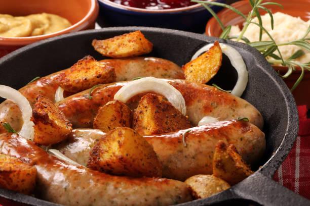 wurst mit kartoffeln in einer pfanne gebacken - knoblauchkartoffeln stock-fotos und bilder