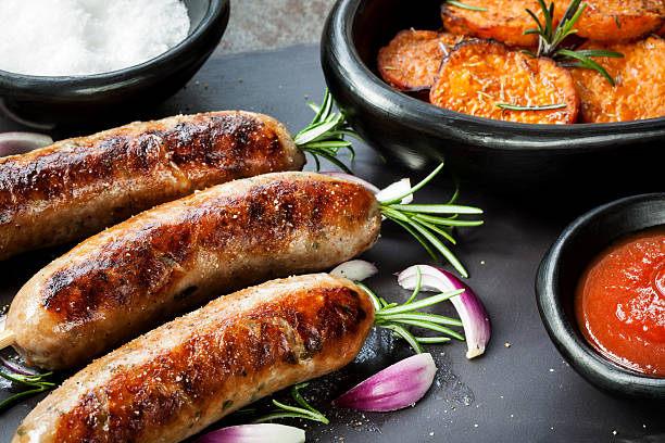 Sausages with Rosemary and Sweet Potato Fries stock photo