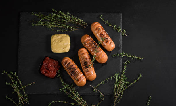Sausages with sauces and thyme on black background. Top view. stock photo