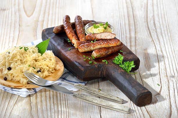 wurst mit sauerkraut - bratwurst mit sauerkraut stock-fotos und bilder