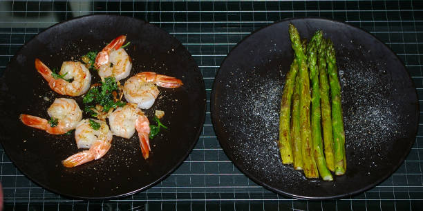 Sautéd shrimp and green asparagus appetizers stock photo