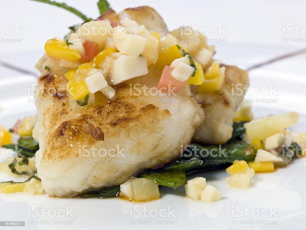 Saute Sea bass with mango-tropical fruits sauce stock photo