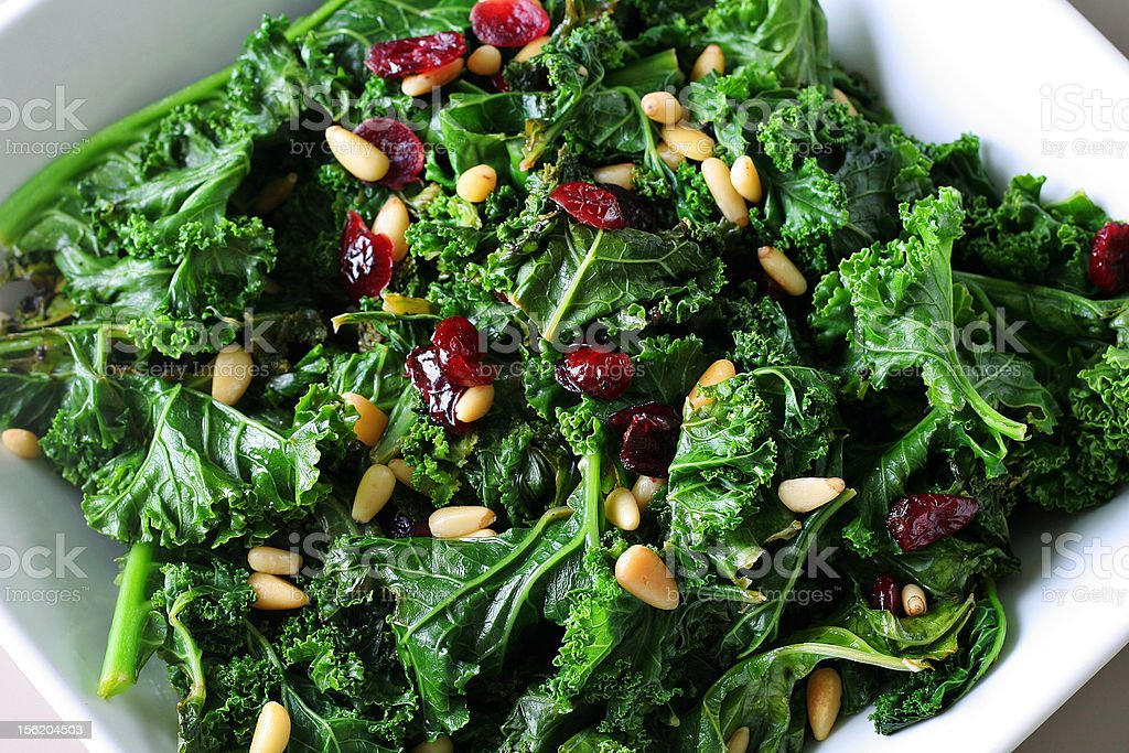 sauteed kale with cranberries and pine nuts stock photo