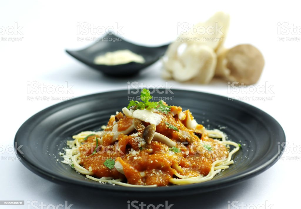 Sauteed mushroom with tomatoes sauce and ramen noodle on black dish royalty-free 스톡 사진