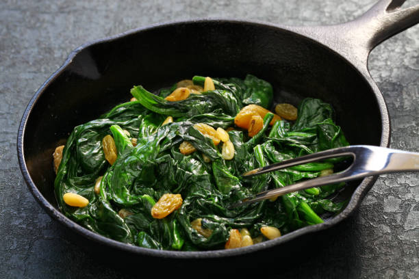 sauteed spinach with raisins and pine nuts, spanish catalan dish sauteed spinach with raisins and pine nuts, spanish catalan dish catalonia stock pictures, royalty-free photos & images