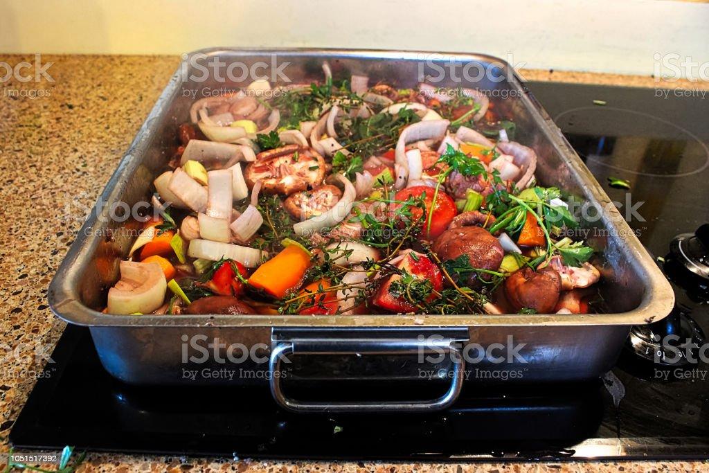 Sauteing uma assadeira cheia de legumes e ervas - foto de acervo