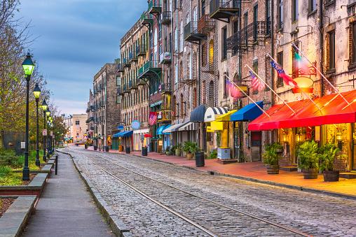 Savannah, Georgia, USA bars and restaurants on River Street at twilight.