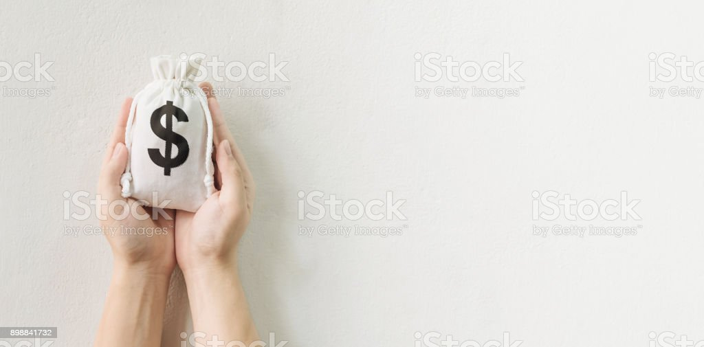 Save money and investment concept, Hand holding money bag with space for your text stock photo