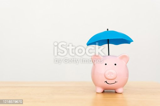 929887844 istock photo Save money and investment concept. Piggy bank and umbrella on wooden table and copy space 1218579670