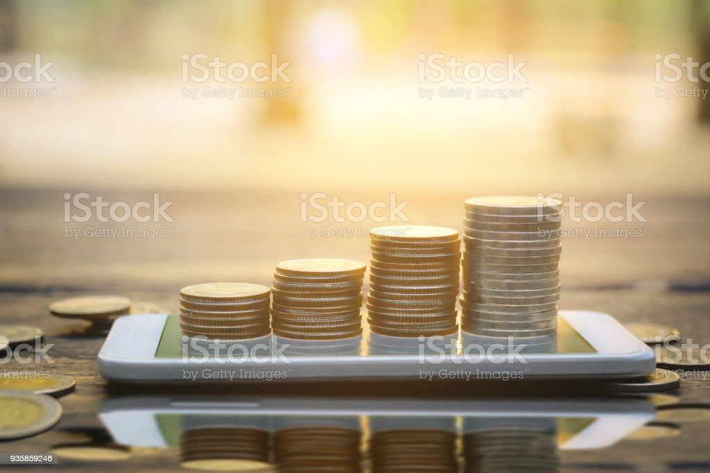 Save money concept with Coin stack growing on smartphone abstract sunset background Save money concept with Coin stack growing on smartphone abstract sunset background Bank - Financial Building Stock Photo