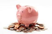 お金を節約し、個人的な財政の財政計画とは、白の背景に分離ブロンズと銀の色のコインの山の上に座ってピンクの貯金箱のテーマと倹約の概念