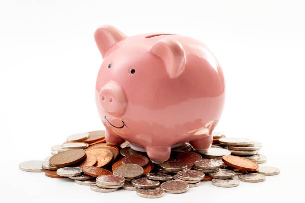 Ahorre dinero, planificación financiera de las finanzas personales y ser un tema de concepto ahorrativo con una alcancía rosa sentada sobre una pila de monedas de color bronce y plata aisladas sobre fondo blanco - foto de stock