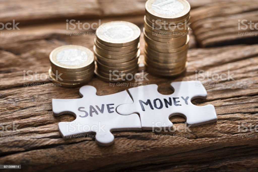 Save Money Jigsaw Pieces By Stacked Coins Stock Photo - Download