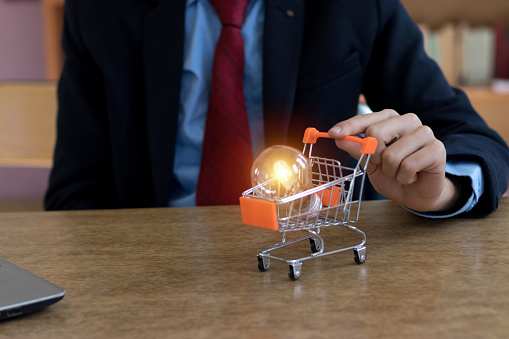 istock save money on shopping/holding light bulbs 1180633874