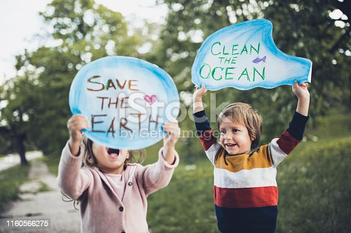 Happy kids holding placards for environmental conservation at the park. Focus is on boy.