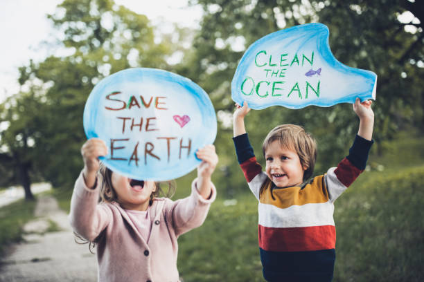 Save our childhood by saving the environment! Happy kids holding placards for environmental conservation at the park. Focus is on boy. rescue stock pictures, royalty-free photos & images