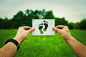 Man hands holding a white paper sheet with bare feet symbol inside over a green meadow background out of the crowd surrounded by nature. Lone traveler, first human walk, save planet concept .