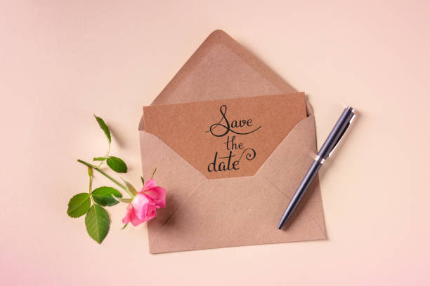 Save the date, handwritten text on an invitation in a craft envelope, shot from the top stock photo