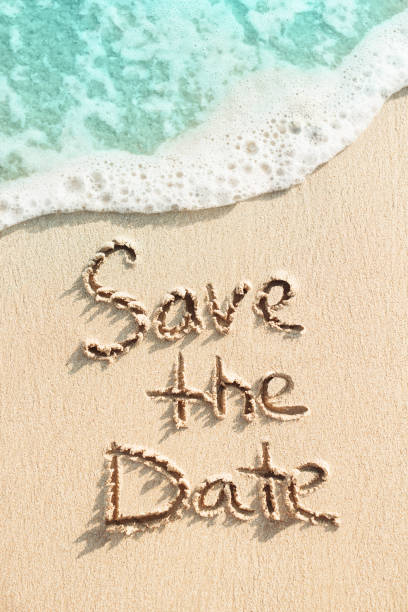 Save the date is written on the sand stock photo