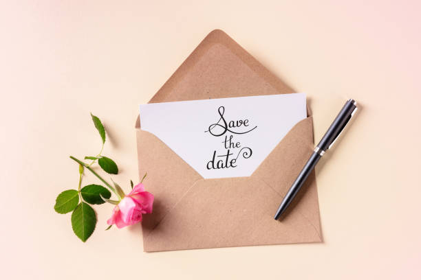 Save the date lettering on an invitation in a brown kraft envelope, shot from above on a pink pastel background stock photo