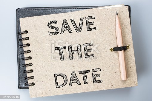 istock Save the date, Text message on brown Notebook / business concept 977279710