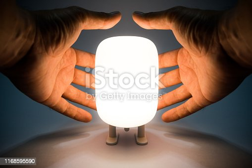 People hand is covering on the cute design table lamp which is turning-on the light in cool white color. Idea of saving energy concept photo.