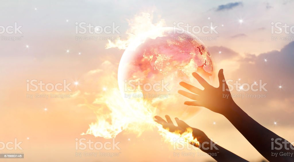 Save the world energy campaign. Planet earth with flame on human hands show energy consumption of humanity at night, Elements of this image furnished by NASA stock photo