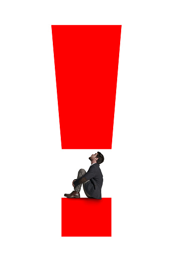 Shot of an unrecognisable businessman stuck in between an exclamation mark against a white background