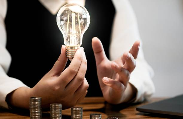saving coins idea with light bulb for investment Concept idea and innovation. stock photo