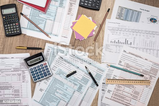 saving concept - tax form, budget, notepad, pen, calculator