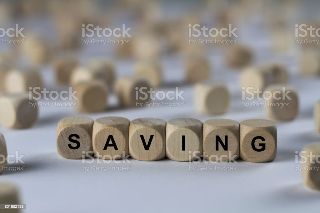 saving - cube with letters, sign with wooden cubes stock photo