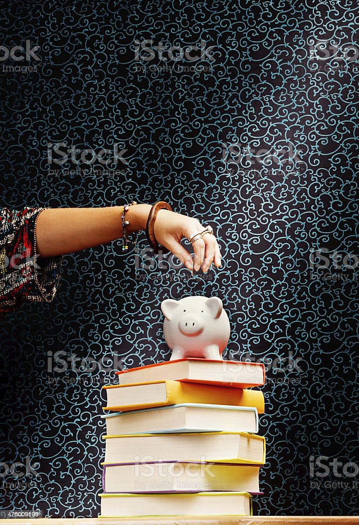 Saving for an education: hand adding coins to piggybank royalty-free stock photo