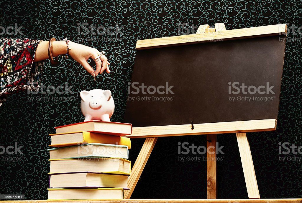 Saving for an education: hand puts money into piggybank royalty-free stock photo