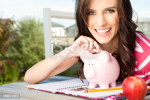 Happy college student inserting money in piggy bank
