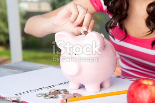 College student inserting money in piggy bank