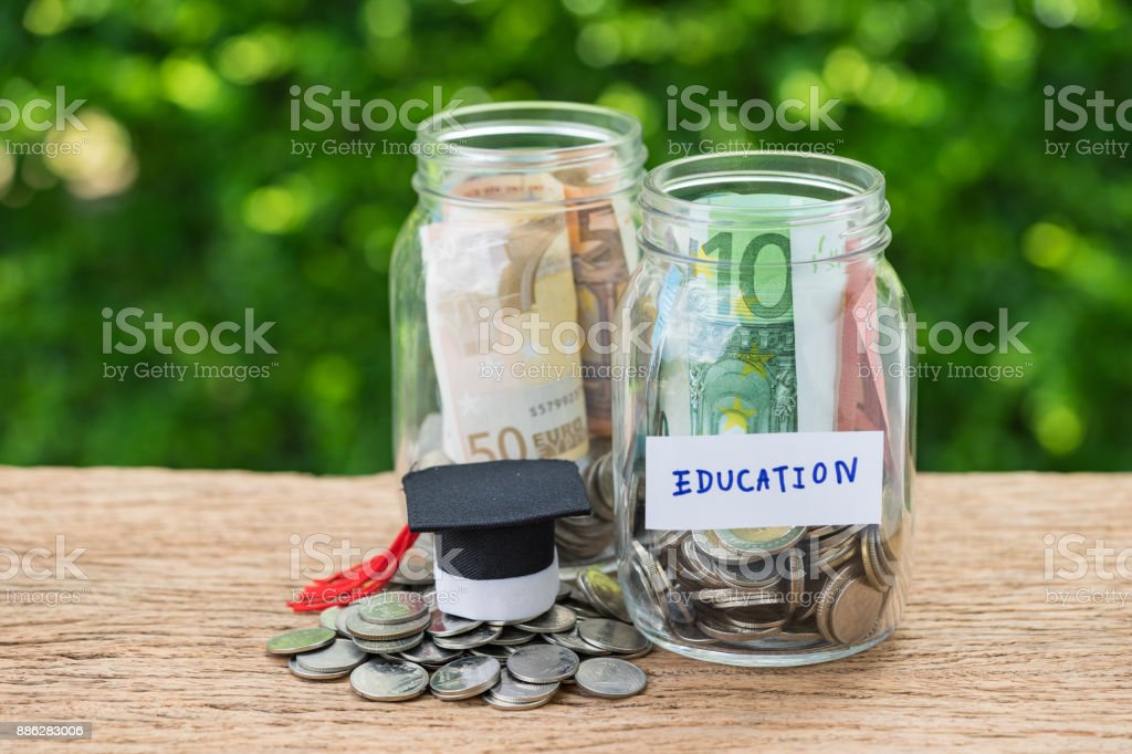 Saving for Education concept as coins in jar with text Education and mini graduation hat on wooden table and green bokeh background stock photo