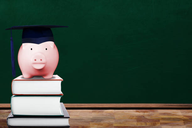 Saving for Education Concept with Piggy Bank and Graduate Hat in Classroom stock photo