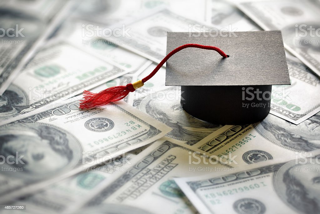 Saving for education Graduation mortar board cap on one hundred dollar bills concept for the cost of a college and university education 2015 Stock Photo