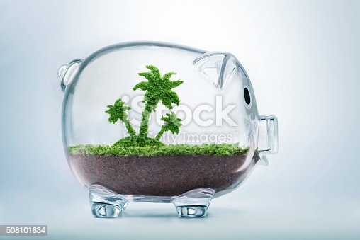 Saving for vacation concept with grass growing in shape of a palm tree inside transparent piggy bank