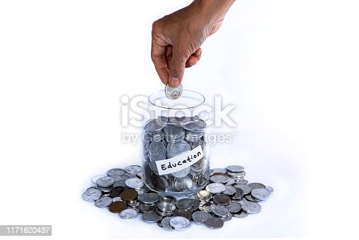 Saving idr coins in the glass bottle jar for vacation on white background wirh copyspace