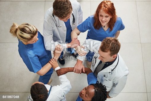 High angle shot of a group of medical practitioners joining their hands together in unity