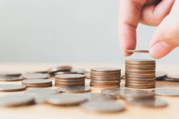 お金を貯蓄と投資が成長を裕福な成長していると持続可能な未来のため、男性または女性の置くコイン スタックの手ステップ成長成長金融 ストックフォト