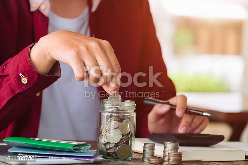 Saving money concept asian man hand putting coin write cost and Finance. expenses calculator, payments costs with paper notes, Financial and Installment payment concept. Saving concept