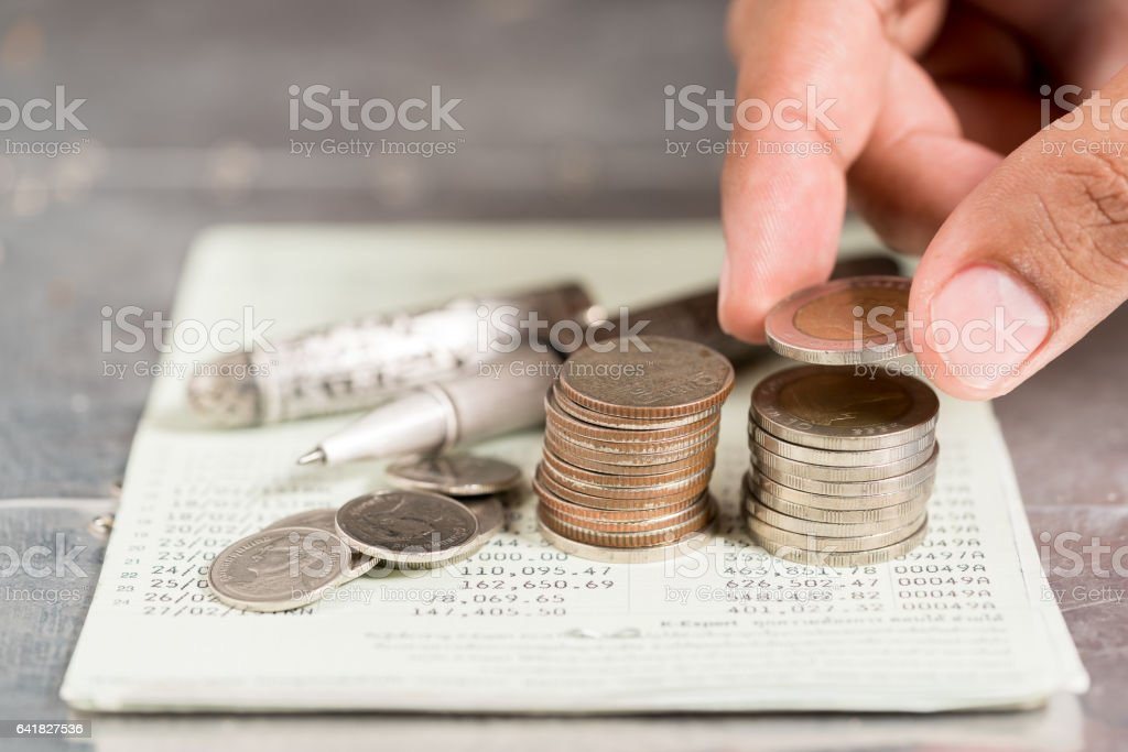 Saving money concept  by Male hand putting money coin stack stock photo