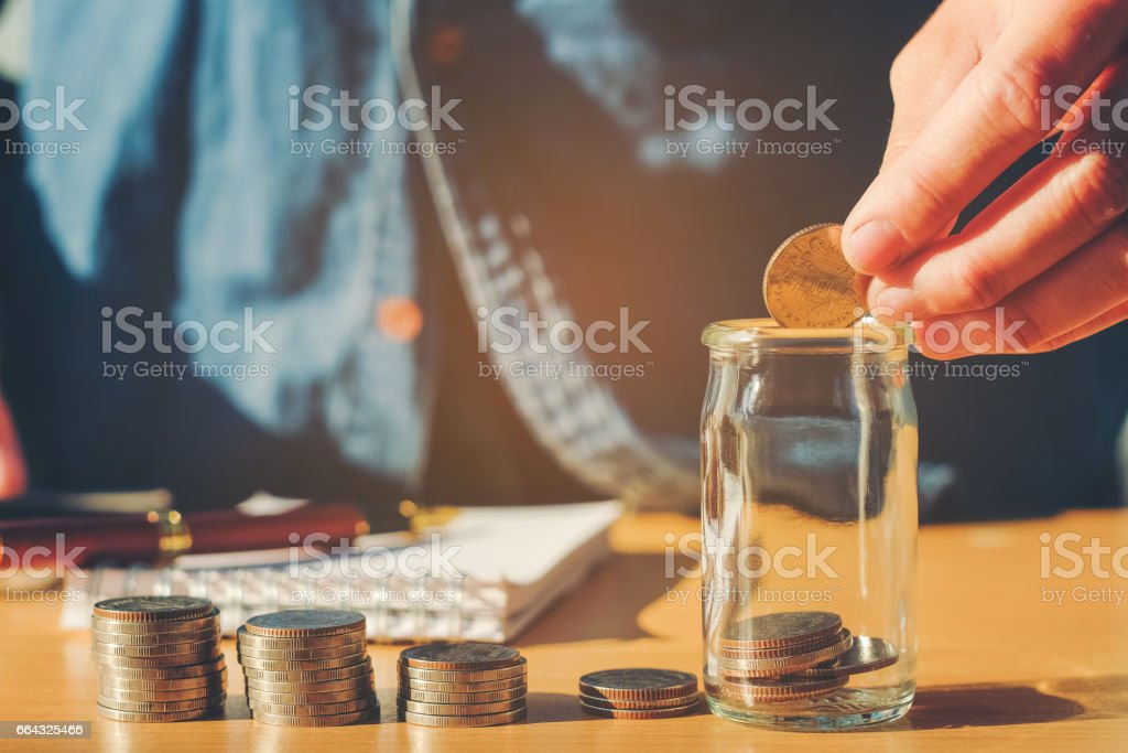 Saving money concept Man hand putting Row and coin Write Finance stock photo