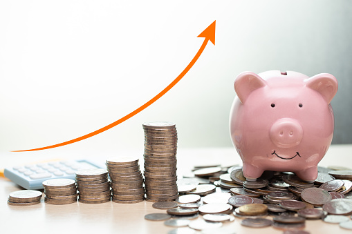 istock Saving money concept.business rich income show as stack money coin growing arrow with piggy bank smile over coins pile. 1168106660