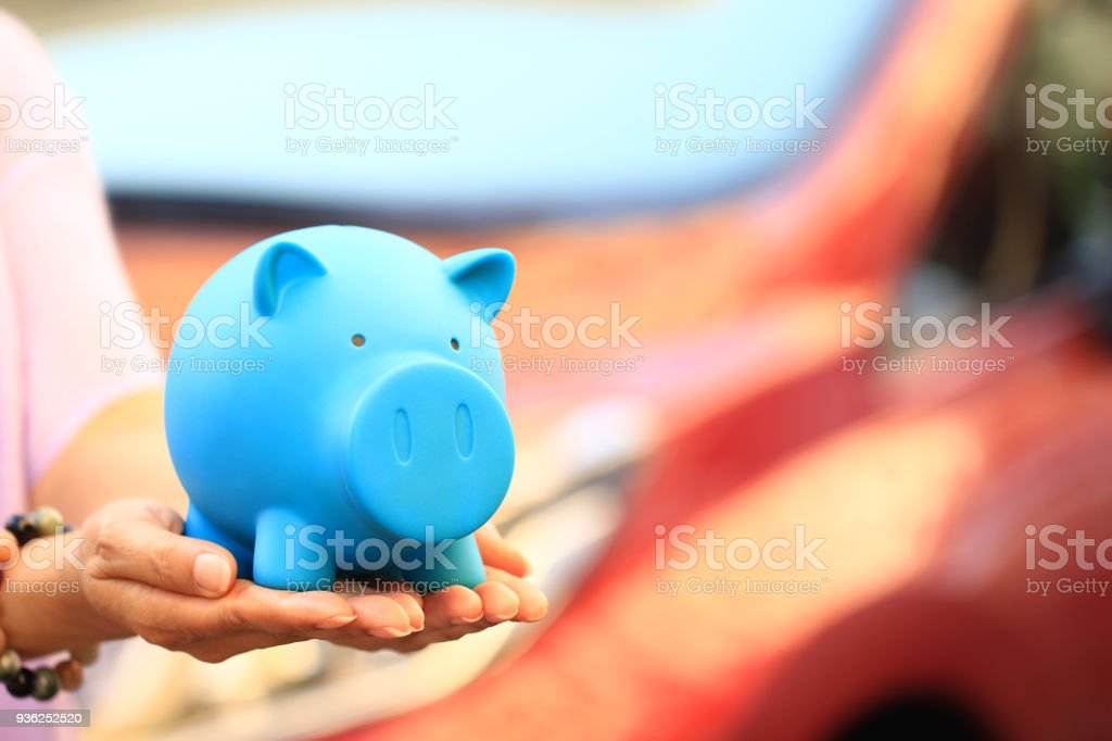 Saving money for car concept, Young woman holding blue piggy with standing at the car parking lot background, Auto business stock photo
