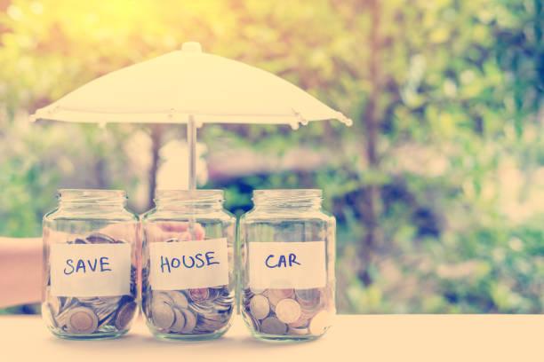 économiser de l'argent pour la maison et une voiture concept: pièces de monnaie en bocaux sous un parapluie. idées d'épargne pour un acompte sur une voiture ou une maison qui permettent aux acheteurs d'acompte permet de réduire le coût global de l'emprunt - prêts immobiliers et crédits photos et images de collection